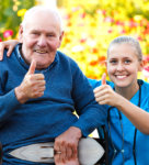 caregiver and old man showing their thumbs up