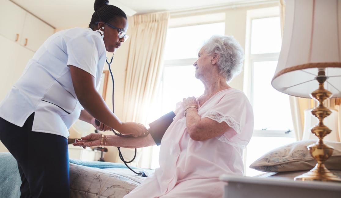 caregiver getting the blood pressure of elderly patient